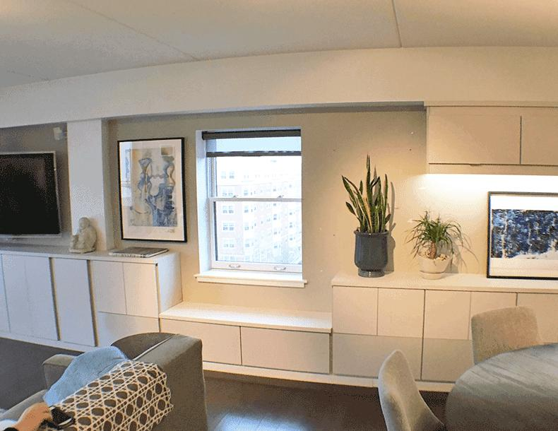 Family Room Wall Storage with White and Light Grey Cabinets Counter Tops and Bench Seating