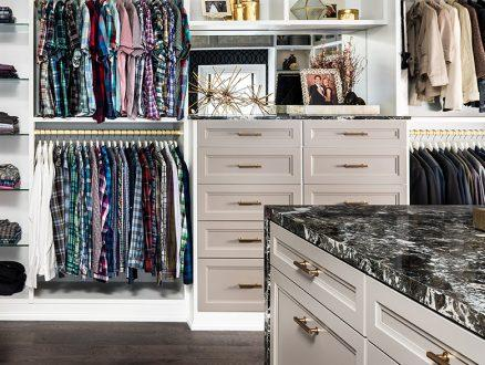 White and Gold Themed Walk in Closet Glass Shelves Gold Closet Rods and Light Grey Dresser Drawers